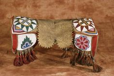 "Cree beaded pad saddle 18""(l) with beaded tabs, floral and geometric designs in red, blue, green, pink and butterscotch. The yarn tassles have glass tubular beads.There is an old label that reads ""Indian Saddle - said to have belonged to Sitting Bull's daughter"". Fine cond, circa 1890"