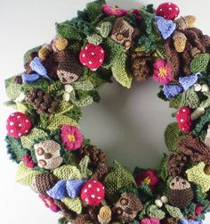 Free Knitting Pattern for Woodland Wreath - Designed by Frankie Brown, this knitted cover for any size wreath features hedgehogs, owls, leaves, flowers, mushrooms, pine cones, acorns and other woodland flora and fauna.