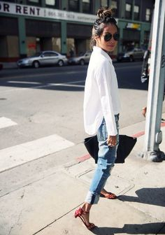 Step up your off-duty look in a white oxford shirt and blue jeans. Red leather heeled sandals are a great choice to complete the look. Shop this look on Lookastic: https://lookastic.com/women/looks/dress-shirt-jeans-heeled-sandals/17372 — Black Sunglasses — White Dress Shirt — Blue Jeans — Black Leather Tote Bag — Red Leather Heeled Sandals