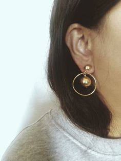 """Minimalist statement earrings in gold tone vintage 80's costume jewelry.  Two moveable balls with swinging hoops. Very lightweight and in great  condition, no marks or scratches.  Height: 1.5"""" /Width: 1"""""""