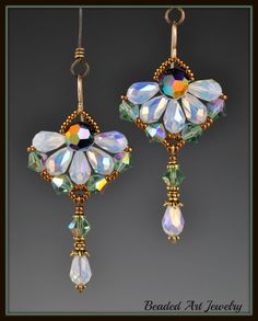 "Via Etsy: These pretty earrings are woven together to create a flower, with Swarovski 9x6 White Opal ab crystal drops and 6mm Erinite ab crystal bicones. There is an 8mm round Jet ab2x crystal in the center and the earring wires are gold filled.  They measure 2 3/8"" long and are 1 1/4"" wide."