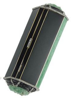 AN ART DECO ONYX, JADE, ENAMEL, PÂTE DE VERRE AND DIAMOND VANITY CASE. The octagonal case, applied with black enamel and green 'pâte de verre', to the carved onyx and sculpted jade sides, enhanced with rose-cut diamond details, opening to reveal a mirror, two powder compartments, a lipstick holder and a propelling pencil, 1920s, 10.1 cm, with French assay marks for gold. With maker's mark of Atelier Strauss, Allard, Meyer, numbered.