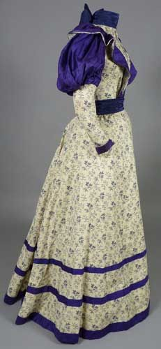 Day dress, 1896. Roller-printed cotton, silk twill; reproduction collar and belt. After 1895, enormous sleeves gave way to slightly tamed puffs, and continued to diminish until sleeves were entirely snug by 1899.