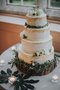 Four tier iced cake decorated with gold leaf and fresh flowers. Photography by Grace Elizabeth