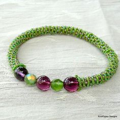 """An original design by KnotGypsy - Simply fun!  Bracelet  is hand knotted with nylon    cord in light green and beaded with lots of  tiny seed beads in green, purple, and amber.  Lovely glass focal beads in green and purple.  Bracelet is a medium - inner circumference is about 7 1/2 inches.  I     design my jewelry to be durable as well as beautiful.  One of the     things I love about beaded micro macrame jewelry is that it feels so     """"friendly"""" in the hand and is comfortable to wear."""