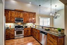 Stainless steel appliances, gas range, and endless granite counter tops with tile back splash combine to create a stylish yet functional kitchen.