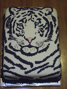- White tiger cake covered in fondant, black stripes done in butter cream.  Fondant for whiskers.