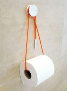 Use a rope to hold your toilet paper storage roll, and add a dash of color to the bathroom. A simple but functional toilet paper storage idea. http://hative.com/clever-toilet-paper-storage-or-holder-ideas/