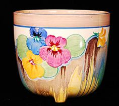 A large Jardiniere by Clarice Cliff in the Delecia Pansies pattern. Size 7 inches high by 7.5 inches wide. Excellent condition. Only a couple of minute losses to the blue. No damage or restoration. Not marked. Price £465.