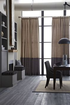 Dark colors can add a richness to a room, but can swing toward ominous and overpowering if you're not selective. Warm browns and gray tones are masculine, and won't weigh down a space. Aim for drapes that rely on a subtle gradient (gray and brown is quite lovely!), so they're not flat or overly dark. A classic lighter rug breaks up the deeper hues, and accessories in various textures (like wooden tray or metallic vase) add another welcome layer of interest. This neutral balance creates a…