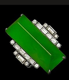 An Art Deco jadeite and diamond ring  The bright apple green jadeite of very good translucency, measuring approximately 28.2 x 11.3mm, carved as an elongated pyramid, flanked by baguette and brilliant-cut diamonds to each side, mounted in platinum, the diamonds estimated to weigh approximately 0.94 carats in total, maker's mark