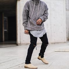 medium grey marled tunnel neck sweatshirt. long light grey tee. black jeans w zippers. tan chelsea boots.