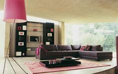 salon spacieux aménagé avec un canapé d'angle marron foncé, un tapis rose et un lampadaire rose élégant