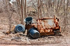Garbage Cans and Rusted Parts - Rusted bins and garbage cans lay next to a muddy trail in Ontario