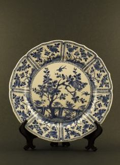 Kangxi - Thinly potted blue and white dish with paneled flower decor and a central garden motif, marked with a Ding censer to the reverse