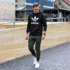 Acheter la tenue sur Lookastic: https://lookastic.fr/mode-homme/tenues/sweat-a-capuche-imprime-noir-et-blanc-pantalon-de-jogging-olive-baskets-basses-en-cuir-blanches/18768 — Sweat à capuche imprimé noir et blanc — Pantalon de jogging olive — Baskets basses en cuir blanches