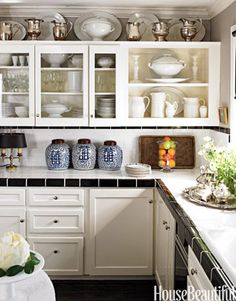 """""""The kitchen is a good size, but small by Dallas standards — only about 16 x 16,"""" designer Craig Schumacher says of this Texas kitchen in the house he shares with partner Philip Kirk. They avoided an extensive kitchen remodel by painting existing cabinets Benjamin Moore Brilliant White and installing inexpensive black and white tile on counters and backsplashes. An extensive ironstone collection overflows from shelves to walls. Vintage jurors' chairs were picked up at assorted flea markets…"""