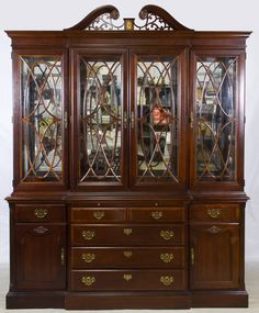 Lot 80: Mahogany China Cabinet by Stanley Furniture; Two piece cabinet with top piece having a split pediment, glass sides and four wood framed glass doors with wood lattice, lower section having quarter drawers over three center drawers and wood panel end doors
