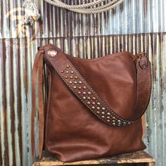 - The softest rustic brandy colored leather tote - Beautiful distressed variation in the natural leather - Metal stud accented strap - Brass, copper and silver parachute studs - Small contrasting copp