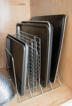 A simple metal rack keeps pans and cookie sheets neat and organized Seven quick and simple budget-friendly kitchen organization ideas to whip your kitchen cabinets and drawers into shape and keep them clutter-free! Small Kitchen Organization, Diy Kitchen Storage, Organization Hacks, Organized Kitchen, Smart Storage, Diy Organizer, Cabinet Organizers, Cabinet Storage, Interior Simple