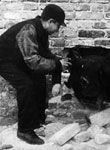 Link to Oneg Shabbat hidden archive from Warsaw ghetto. Includes personal diaries, photos, letters, drawings. This photos is of children being helped through a hole in the perimeter wall through which they smuggled food