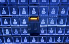 Inside the Suishoden In the Suishoden, blue LEDs illuminate 2,000 small glass cinerariums, each containing a box holding the ashes of a deceased person. Each niche is decorated with an image of the Buddha. The electronic identity card used to access the room will ensure the appropriate urn lights up in gold.