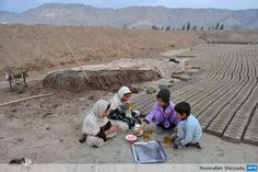Afghan siblings take a break as they work at a traditional brick factory on the outskirts of Jalalabad in Nangarhar province on January 25, 2014. (Noorullah Shirzada/AFP)
