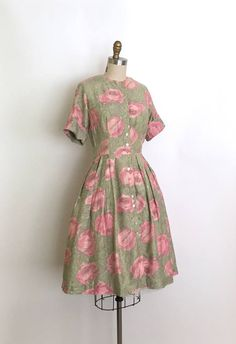 Breath taking shirtwaist dress that features a stunning large rose and leaf print. A delicious colour palette of pinks and greens. The dress buttons up the front and has a lovely full pleated skirt. A classic cotton dress!