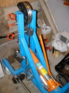 Homemade tube bender fabricated from square steel tubing and powered by a hydraulic jack. Based on a Frank Tacaks design and utilizing commercially obtained dies.