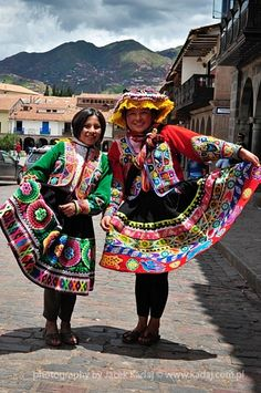 Women in traditional red dresses and hats on the Plaza de Armas in Cuzco, Peru.