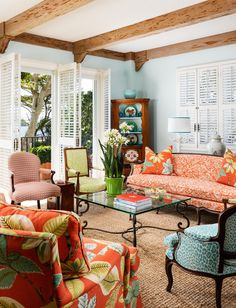 This cheerful living room with its vibrant prints has ample seating for guests, and looks out through bahamian white shutters upon ocean views.