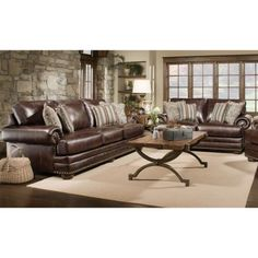 brown leather sofas with white rug, dark hardwood floors & stone accent wall