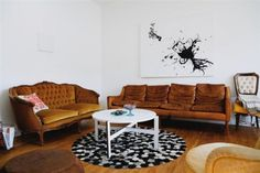 Unmatched sofas paired by repeating elements: B&W print, rung, coffee table.