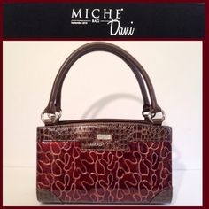 """MICHE Classic Handbag Classic bag is brown with silver hardware. Inside has 3 pockets, one with a zipper. The wrap around shell red and brown is """"Dani"""". 2010, retired. Little feet on the bottom. In perfect condition! Strap drop is 6 1/2 in. Long. Miche Bags Totes"""