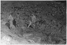 American servicemen inspecting a shell crater after the Japanese attack on Fort Stevens, Oregon. - NARA - 299678