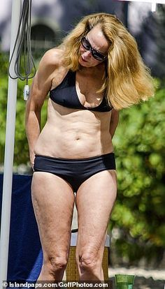 Jerry Hall, wows in skimpy black bikini as she enjoys beach stroll The top model showed off the physique that made her famous, hitting the sand in a black bikini to work on her tan White Swim Shorts, London In March, Jerry Hall, Halterneck Bikini, Black Two Piece, White Caps, Loose Tops, Black Bikini, Physique