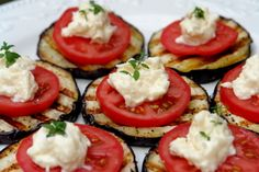 grilled eggplant appetizer bites topped with tomato and a parmesan cheese mixture.
