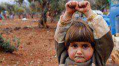 Niña siria atemorizada levanta las manos ante la cámara del fotógrafo creyendo que es un arma.