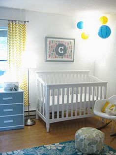 happy blue and yellow gender neutral nursery room crib corner with blue and yellow paper lanterns for crib mobile