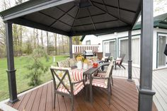 """This dining zone is sheltered by a gazebo overhead. A high contrast screen behind the barbeque creates a cozy kitchen nook. This is an """"AFTER"""" photo from a deck rescue featured on """"Disaster Decks"""" resurfacing project """"The Deck Lucie Hates"""". Deck design by Paul Lafrance Design."""
