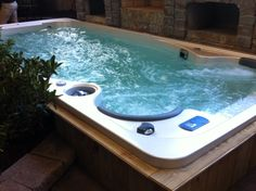 17' Hydropool Swim Spa at the Southern Ideal Home Show. This Hot Spring Grandee is tucked into a beautiful pergola and stone patio. Hot Tub Installation Ideas from Atlantic Spas and Billiards!