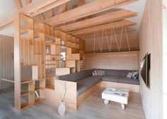 Russian-based studio Ruetemple conjured a plywood partition that  separates working and relaxation areas inside this artist's studio in Moscow, incorporating both furniture and shelves for tidying away art supplies.