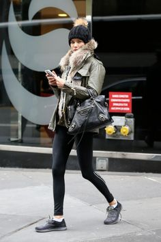 Adriana Lima wearing Victoria's Secret Knockout by Victoria Sport Tights, Sam Kendall Parka in Army and Balenciaga Metallic Edge City Bag