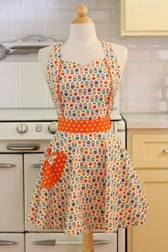 This is a vintage inspired full apron with a sweetheart neckline and tulip shaped pocket! This apron is in a colorful Russian doll pattern. The pocket and straps are an orange and white dot. #apron #apronology #kitchen #retro #baking #cooking #giftforher #vintageinspired #vintagestyle #affiliate
