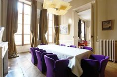 While heavy curtains and chevron flooring would be at home in any antique dining room, the choice of bright purple chairs situates this space in contemporary France.
