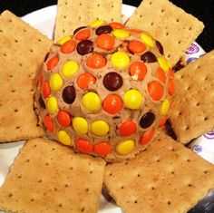 Reese's Peanut Butter Ball 12 oz. cream cheese, softened 3/4 c. powdered sugar 1 tsp. vanilla extract 1 c. peanut butter, warmed in microwave 1/2 c. chopped Reese's peanut butter cups 2 c. Reese's Pieces, for decorating ball Graham crackers, for serving