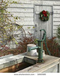 Reminds me - Grandmother's Nebraska farm. http://www.shutterstock.com/pic-1660585/stock-photo-barnyard-with-christmas-wreath-on-white-barn-wagon-wheel-and-water-pump.html