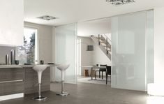 Il sistema Plana Medium di BIHome e Bertolotto Porte, è formato da ante scorrevoli a incasso, con telaio finitura argento e vetro laccato lucido bianco latte