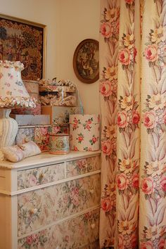 "Oil paintings, 40s or 50s flowered curtains, 40s ""Victorian"" lamp, flowered accessories, dresser with applied flowers on the drawer faces"