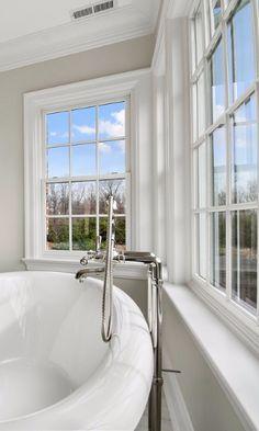 Bathroom with Traditional White-Framed Windows Wrapping Around Bathtub